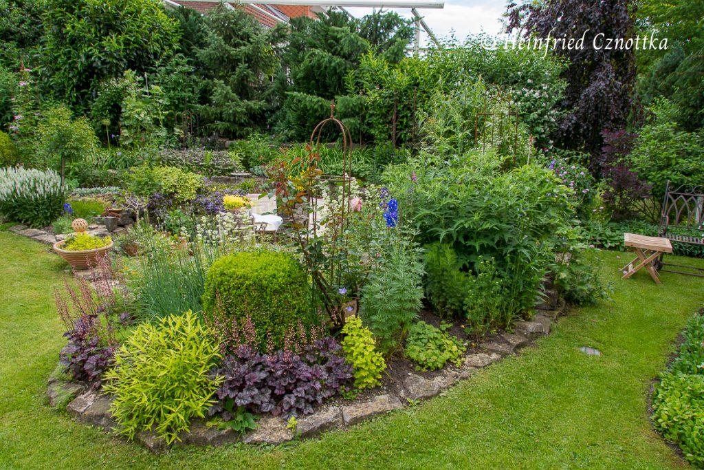 Rosen, hohe Stauden und ein Sommerflieder trennen zwei Gartenräume voneinander.