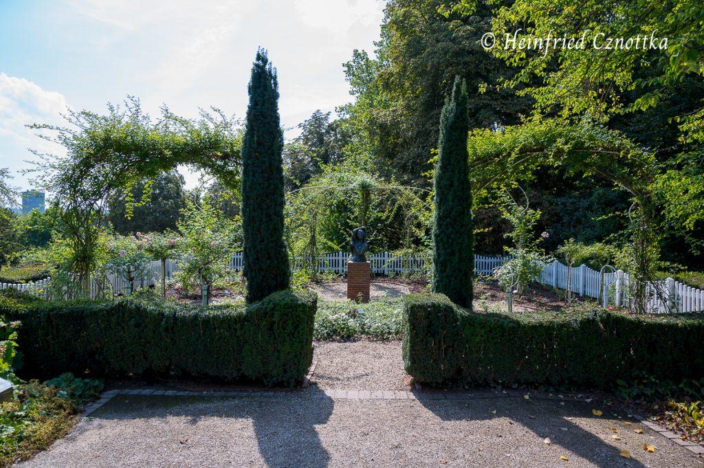 Schlanke Eibensäulen betonen den Garteneingang.