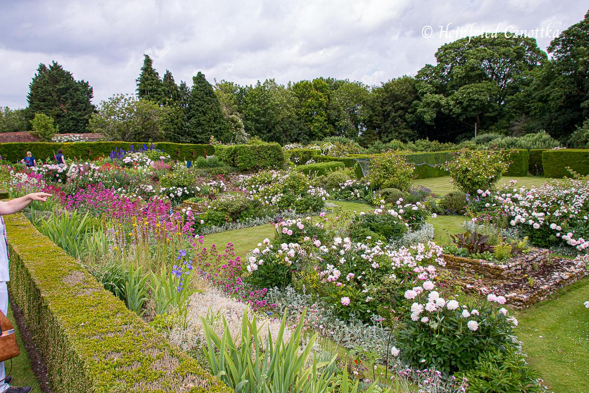 Üppige Beete mit Pfingstrosen, Rosen und Spornblumen