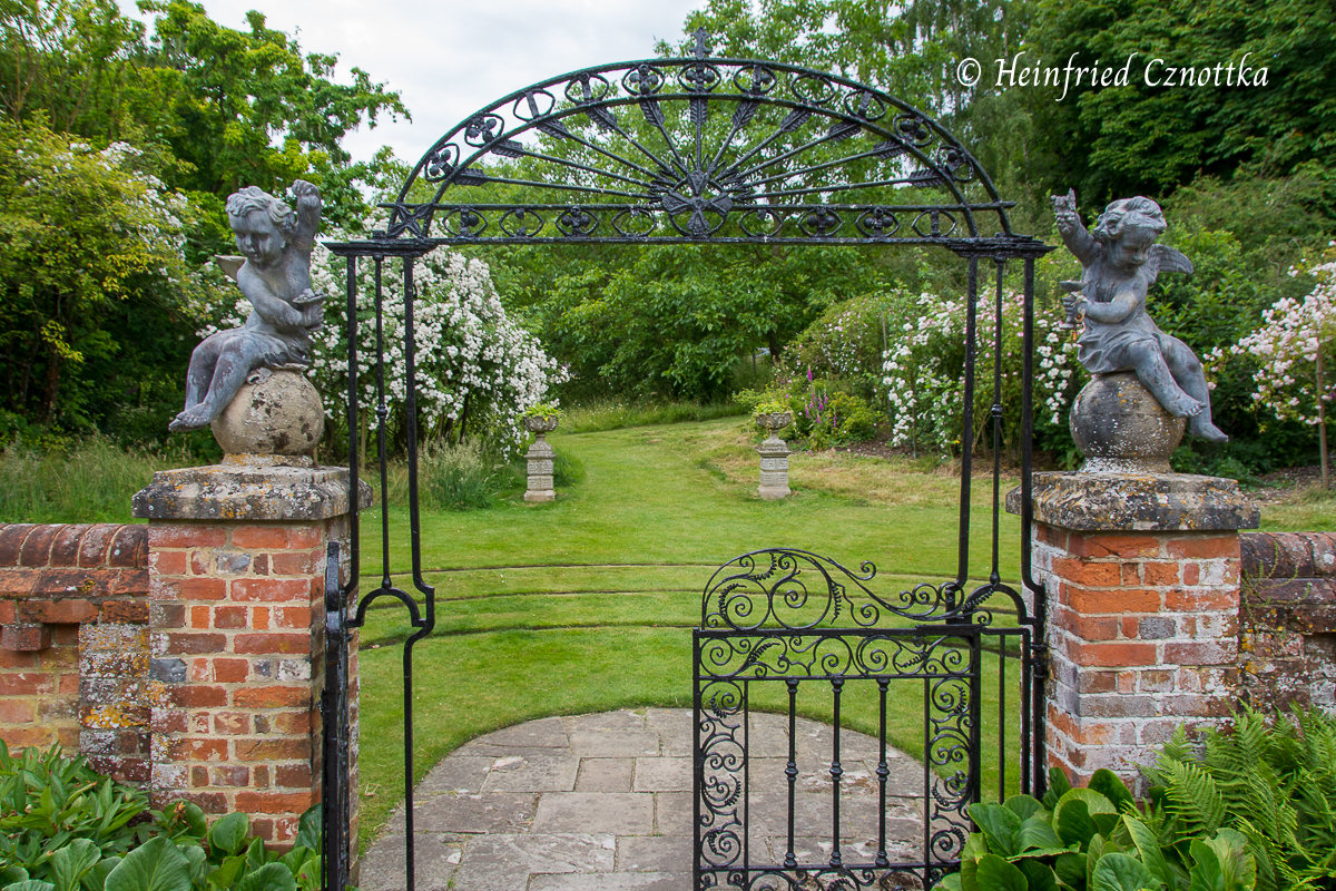 Schmiedeeisernes Gartentor und Putten auf der Mauer von Manor House, Upton Grey