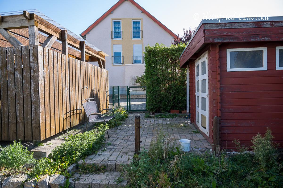 Ein schmaler gepflasterter Bereich zwischen Carport und Gartenhaus